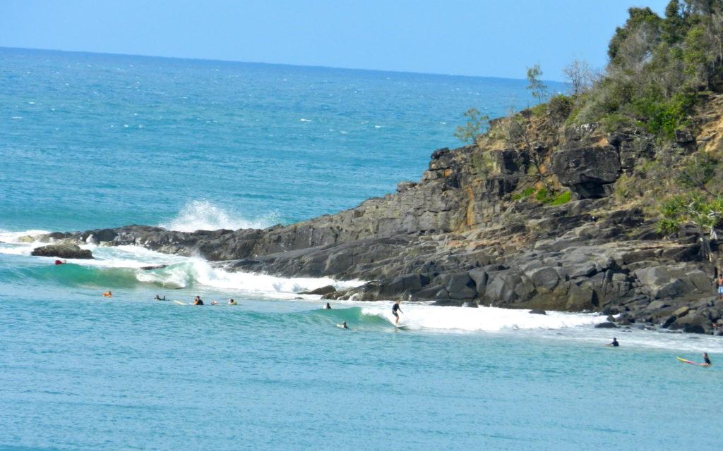 plage, rochers et surfeurs